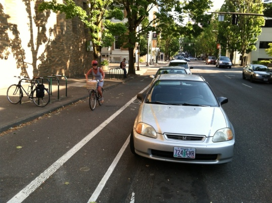 Broadway's cycletrack uses parked cars as a physical barrier between bicyclists and traffic. The city has plans to extend it in 2015.